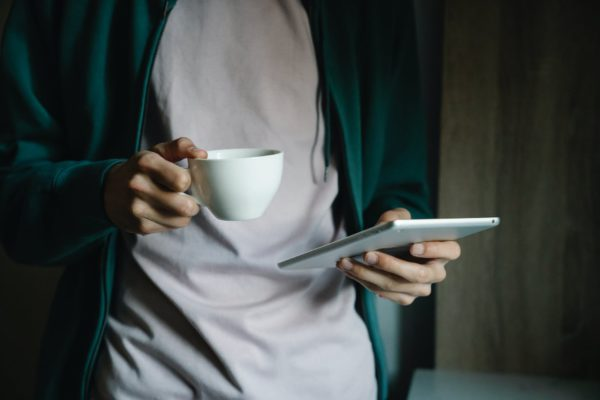 a close up shot of a person holding a cup of coffee and a tablet